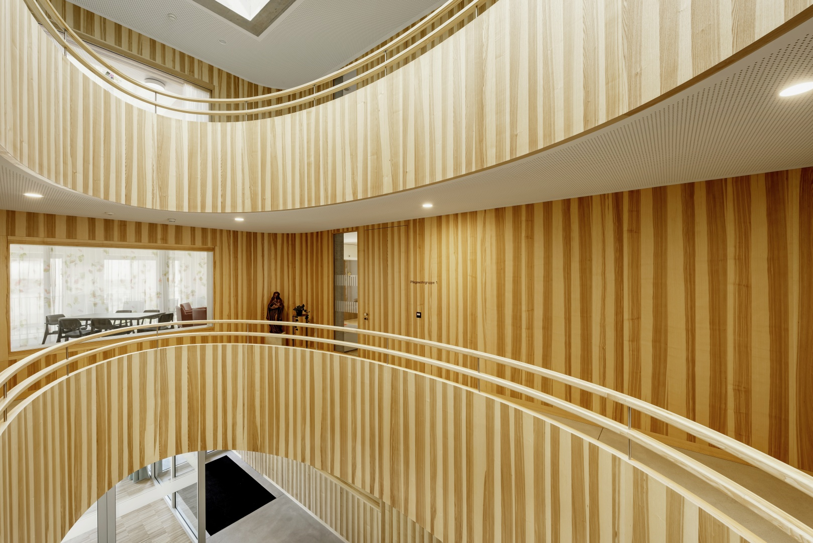 Kerneschenholz bestimmt den Charakter der Innenräume, vor allem im gebäudehohen Atrium, das die Ebenen auch vertikal miteinander verbindet. © Bruno Meier, Sursee