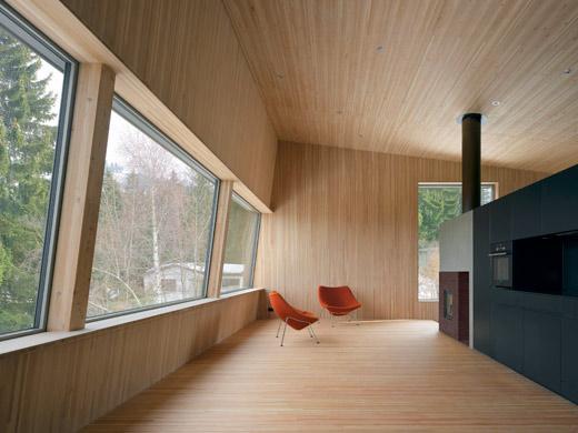 Blick ins Wohnzimmer. Aussenwände, Boden und Dach sind aus tragenden Blockholzplatten (Lärche). © Roger Frei