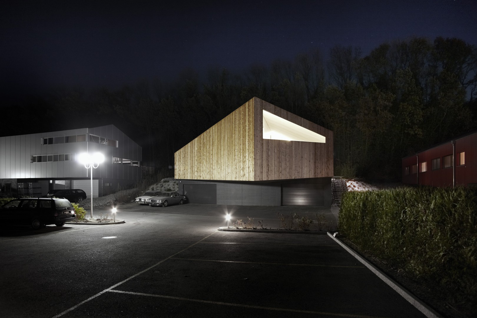 Vue nord: le volume en bois du logement se distingue clairement des garages en béton au niveau de la route © Philippe Joner