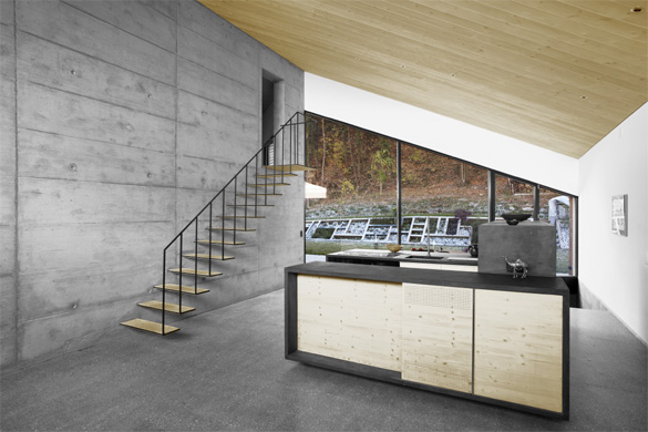 Vue depuis le salon: un seul mur central en béton porte toute la charpente. L'escalier formé de méplat en acier est encastré dans le mur. La cuisine est formé de trois volumes qui organisent le plan en trois sous-espaces: l'entrée (à droite), la © Philippe Joner
