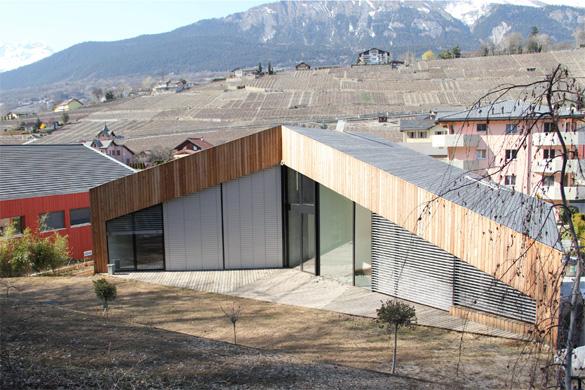 Vue sud-est: le revêtement du toit est en lames de mélèze à l'image de toutes les autres façades. Toute la façade est protégée par des brises-soleil orientables. © Philippe Joner