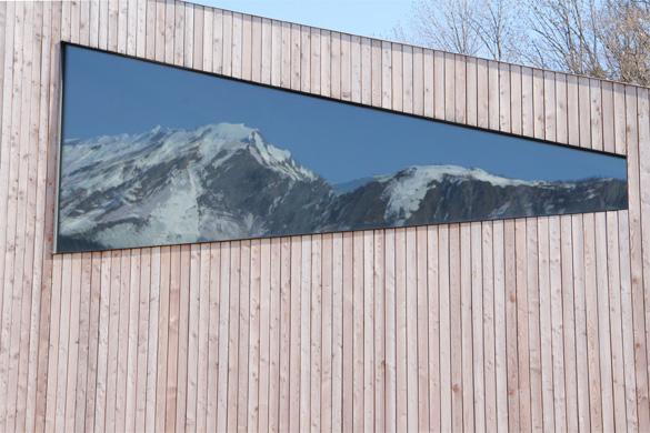 Vue sur la grande baie vitrée qui reflète le massif alpin. Le détail du cadre à été étudié afin de l'affiner au maximum pour le rendre imperceptible. © Philippe Joner