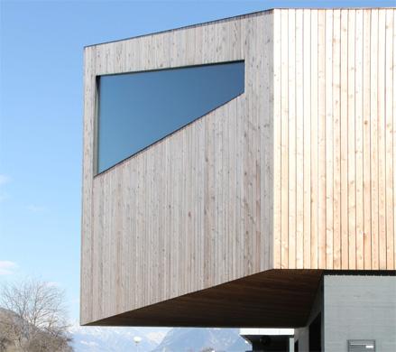 Vue ouest: Le porte-à-faux forme un couvert devant les garages et distingue le volume supérieur par rapport à son socle en béton. © Philippe Joner