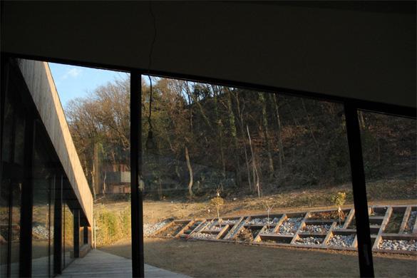 Vue depuis la salle à manger: le jardin et la forêt sont en continuité de l'espace intérieur. La différence de niveau entre les deux terrasses est assuré par une série de cadres en mélèze ayant pour fonction de retenir la terre et de former un  © Philippe Joner