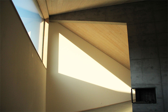Vue depuis le salon. Le soleil du soir rentre profondément dans le bâtiment. La cheminée est encastrée dans la tête du mur porteur en béton. © Philippe Joner