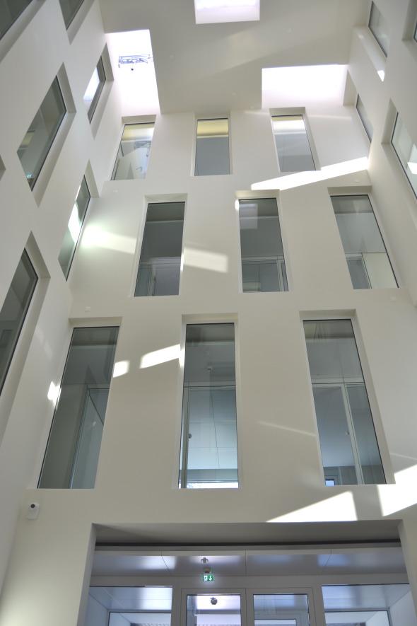 Der viergeschossige Innenhof bietet dem Nutzer diskrete Arbeitsbereiche und sorgt doch für die geschossübergreifende Einheit des Unternehmens.