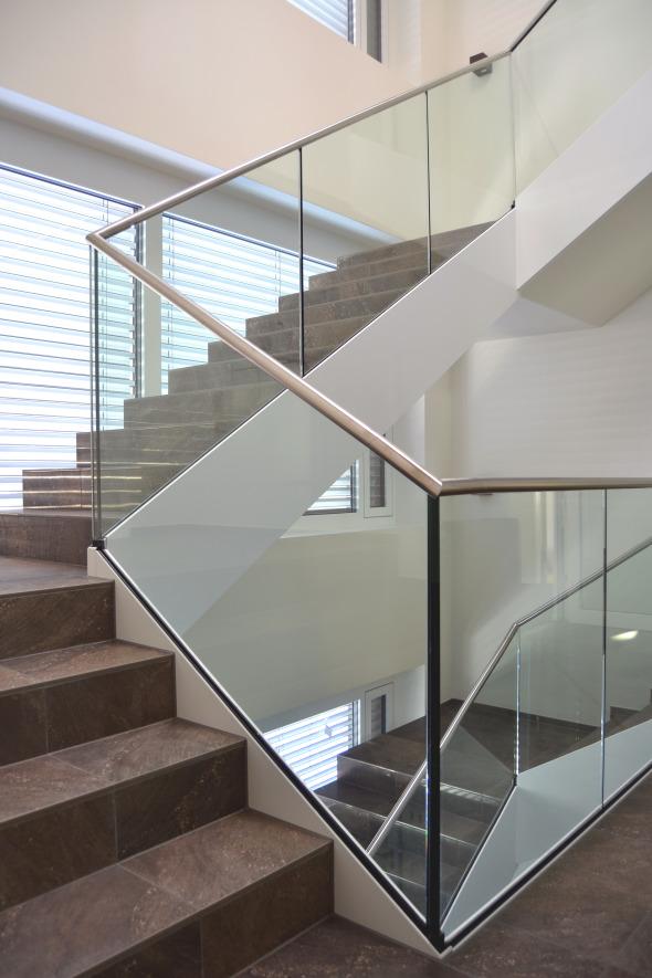 Das grosszügige, lichtdurchflutete Treppenhaus nimmt die Transparenz des Innenhofs auf.