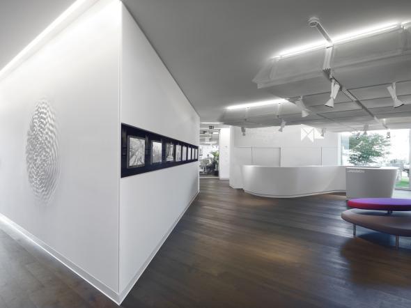 Detailansichten des Empfangs mit Schriftzug in der Theke, Bildschirme in den Wänden © Davide Macullo Architects