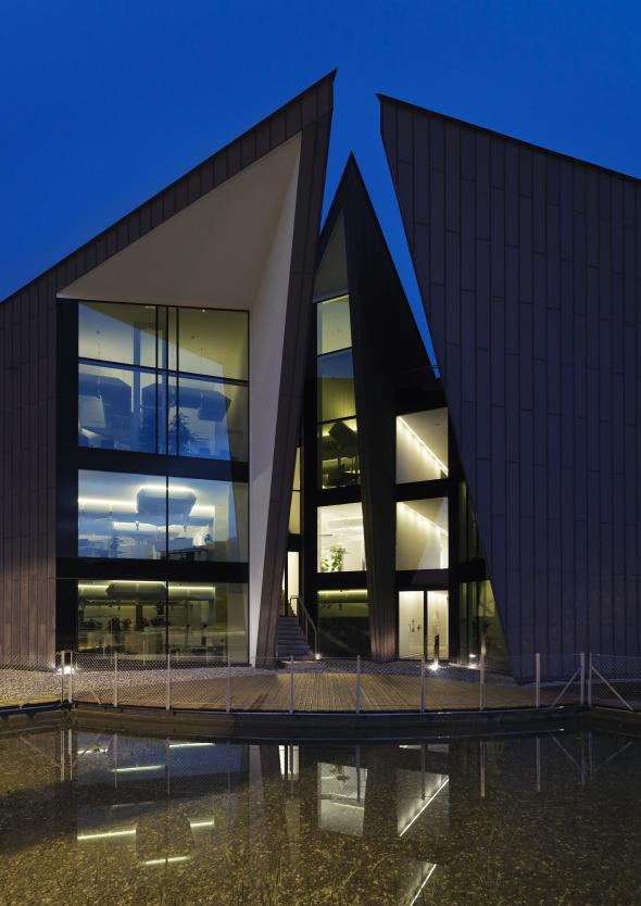 Nachtansicht der Südwestseite, im Vordergrund die Terrasse und der Teich © Davide Macullo Architects