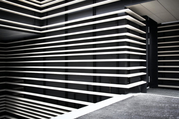 Sichtbar sind bei der offenen Fassade nur die hellen Ton-Baguette, deren Tragprofile und die dunkle Fassadenhaut © Kimlim Architekten