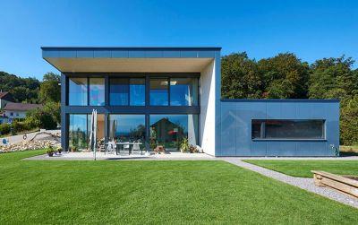 Maison en bois et en verre avec vue sur les Alpes